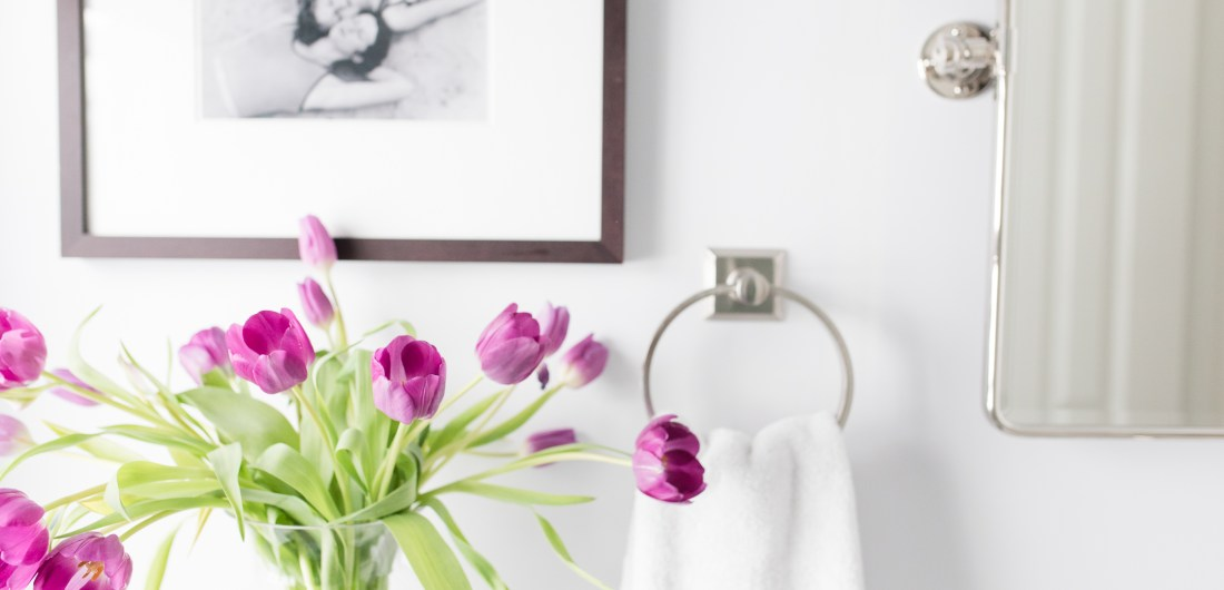 A detail of purple tulips in the bright white guest bathroom of Eva Amurri Martino's Connecticut home