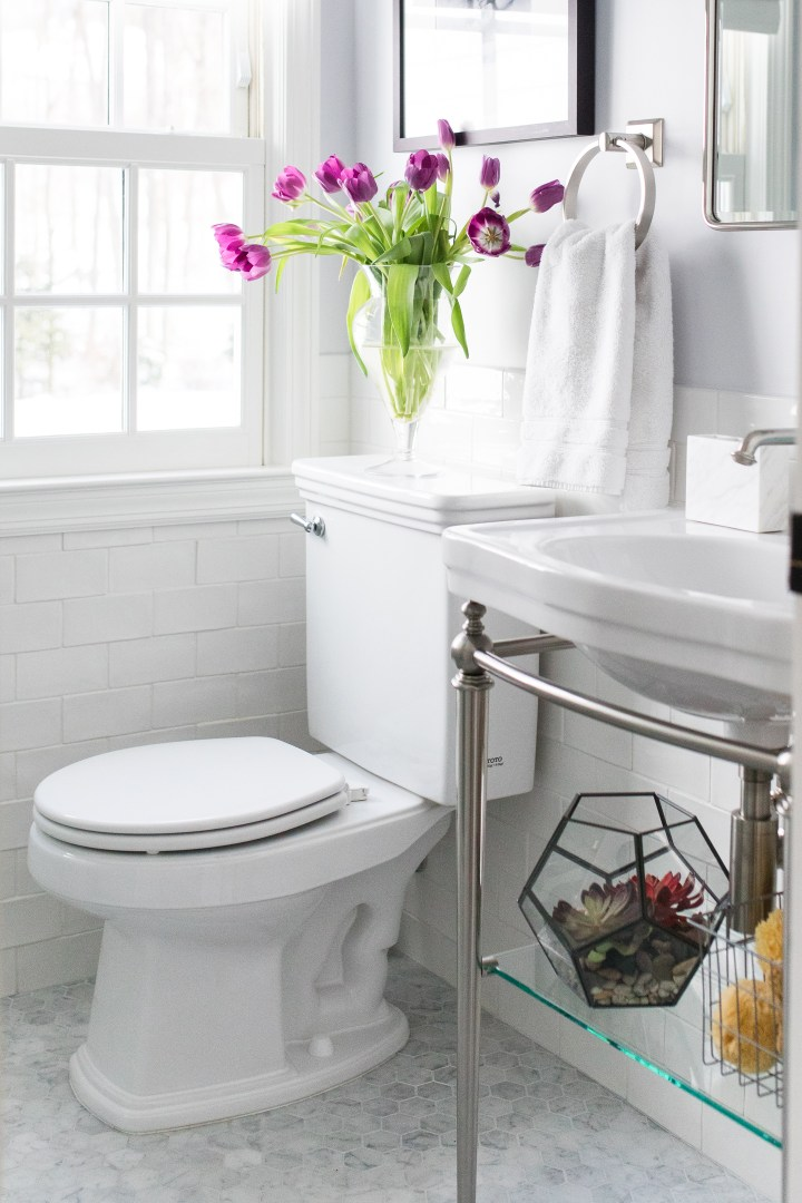 The bright white and chrome bathroom in Eva Amurri Martino's connecticut home, featuring irregular subway tile and marble hexagonal floor tiles