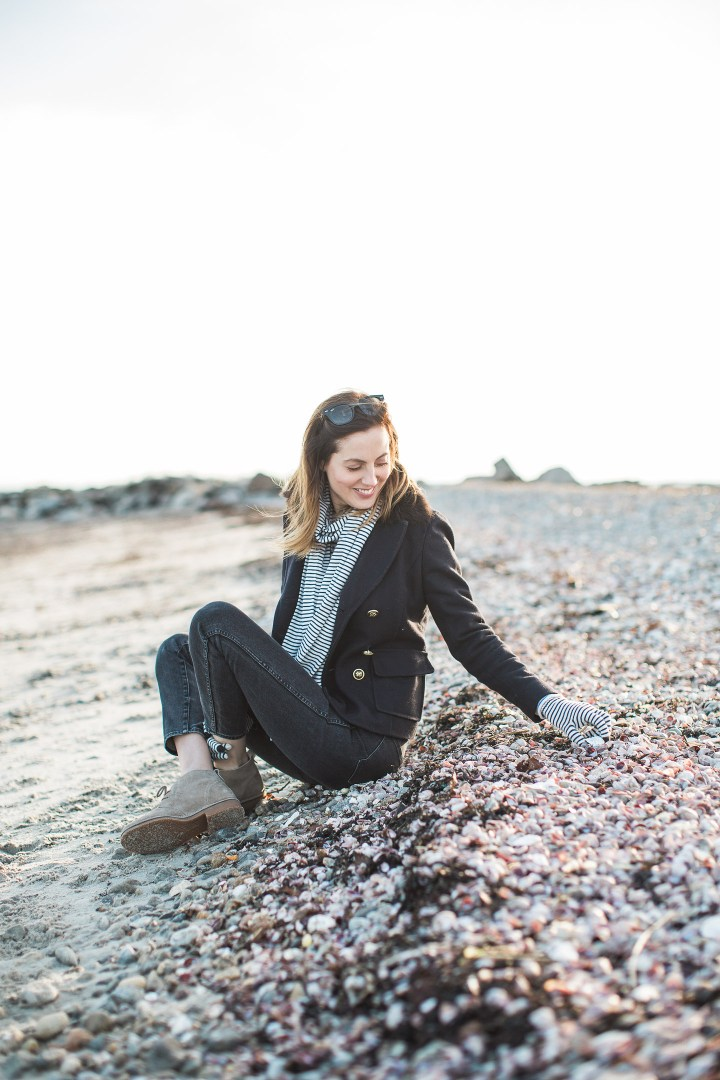 Eva Amurri Martino sits on the sand and picks up rocks in the winter on Compo Beach in Connecticut
