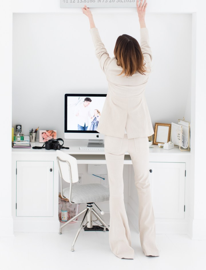 Eva Amurri Martino hangs something above her desk in the Happily Eva After studio