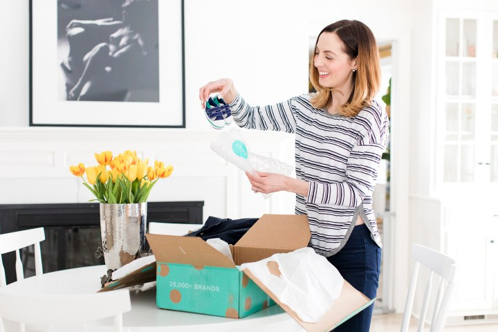 Eva Amurri Martino unpacks a tiny pair of sneakers from her thredUP delivery box