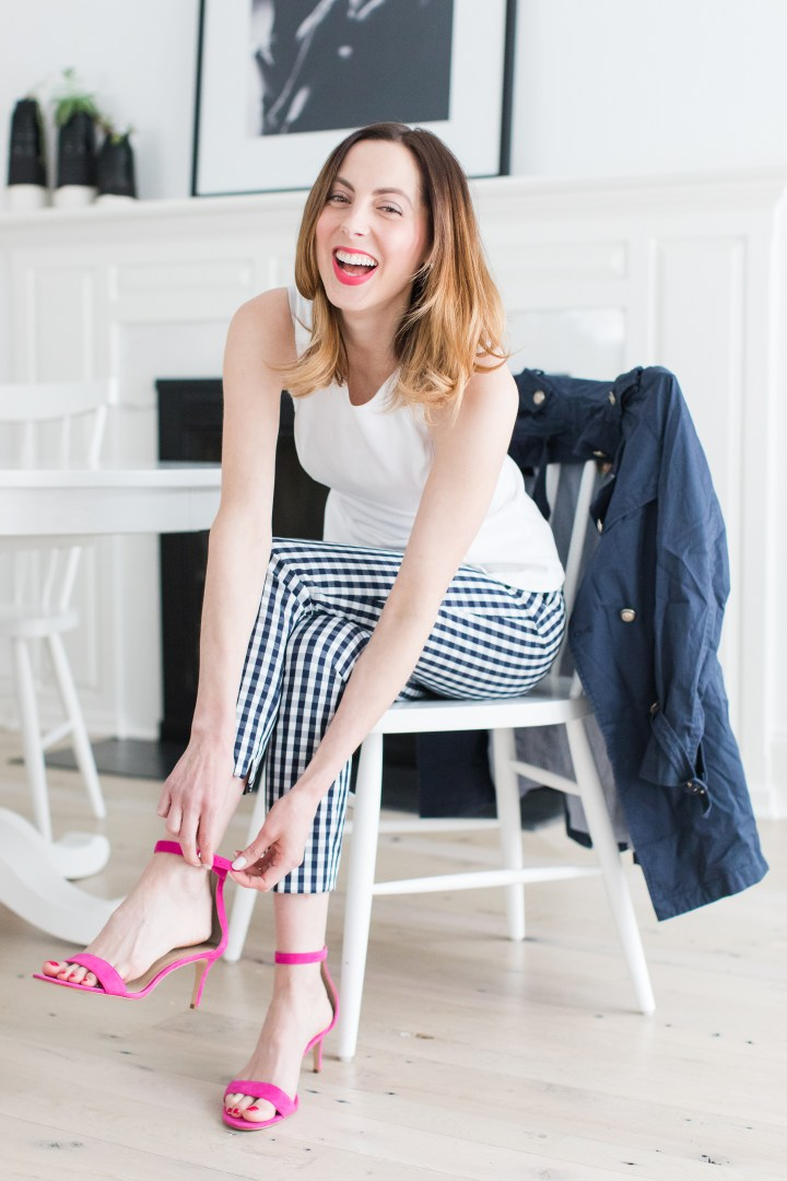 Eva Amurri Martino wears navy and white gingham pants, a white top, and fastens her hot pink heels at the kitchen table