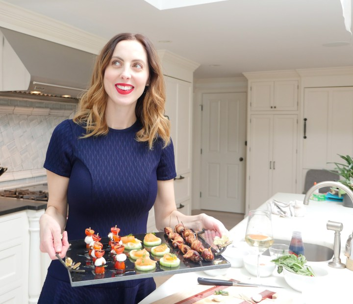 Eva Amurri Martino wears a blue dress and holds a plate of easy to make hors d'oevres as she preps for a cocktail party