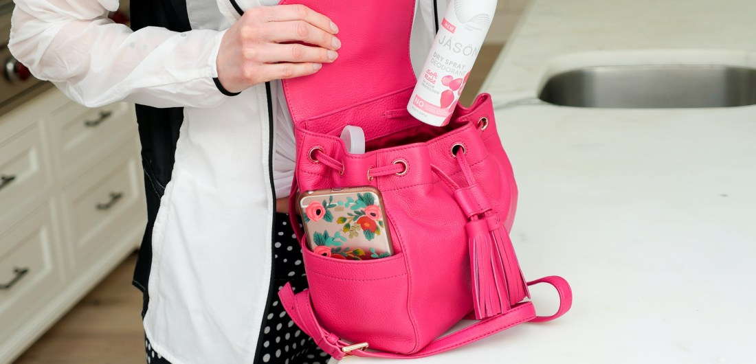 Eva Amurri Martino places a can of JASON dry spray deodorant in to her pink Tory Burch backpack