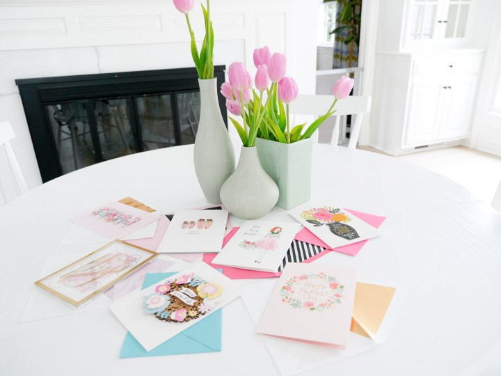 Eva Amurri Martino's white kitchen table is decorated with a trio of vases filled with pink tulips, and an array of mother's day greeting cards