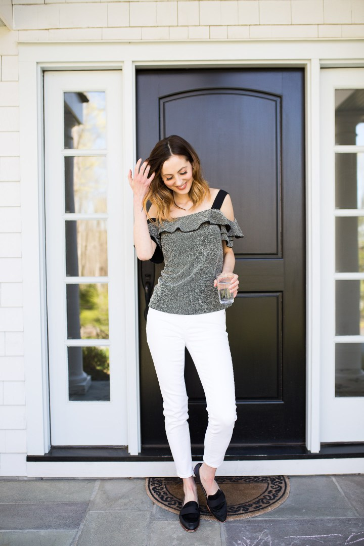 Eva Amurri Martino wears a black top and white jeans in front of her Connecticut home