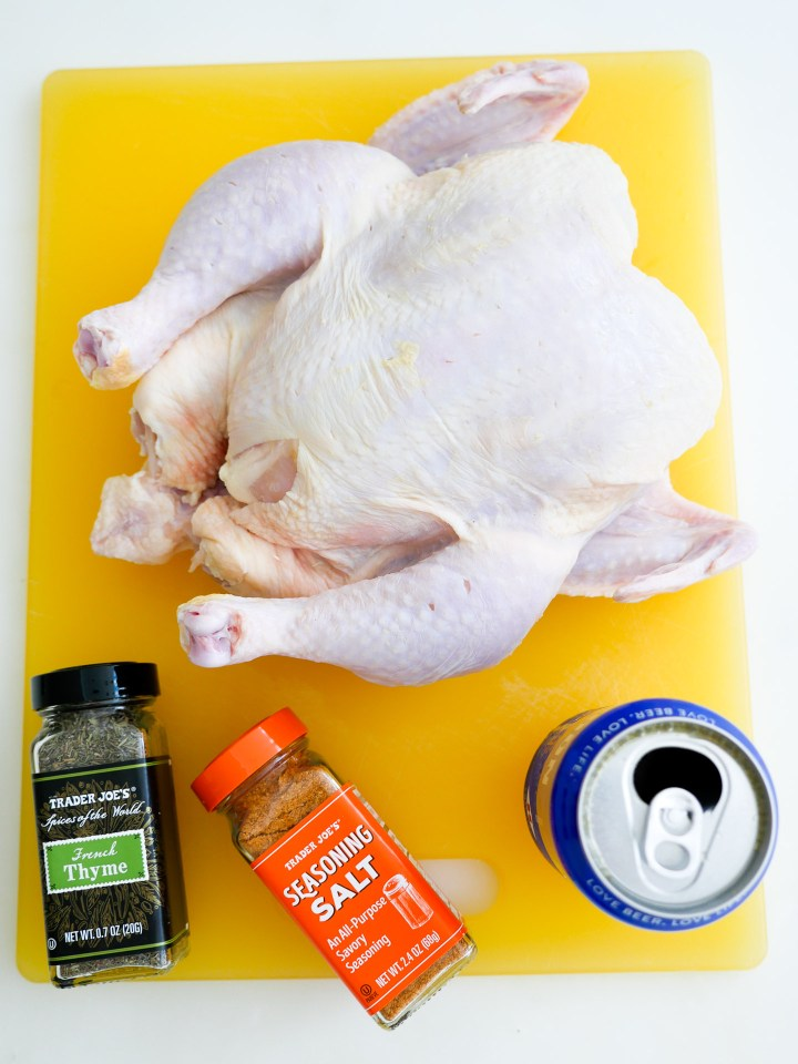The ingredients for beer can chicken sit out on a yellow cutting board, including a raw chicken, beer, and spices