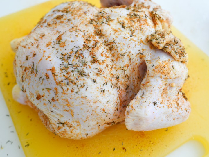 A raw chicken is seasoned with savory seasoning salt and thyme