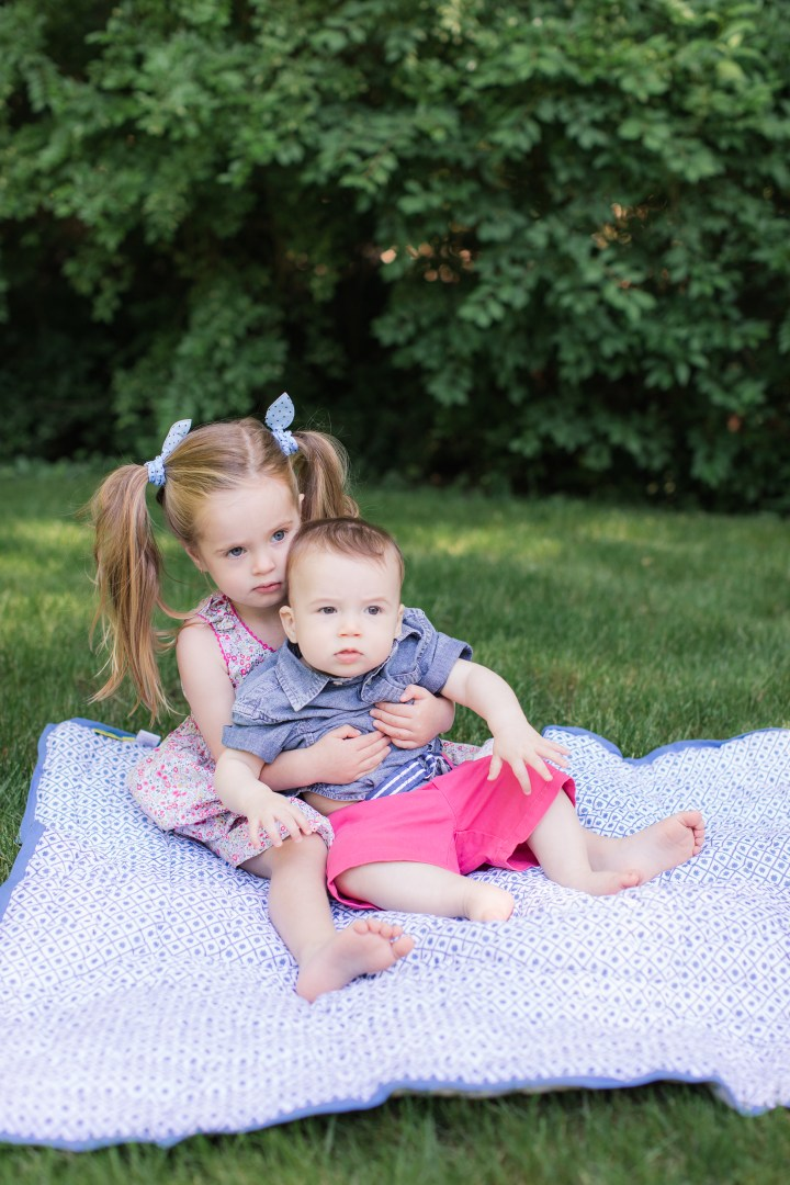 Marlowe Martino holds eight month old brother Major on a picnic blanket on the grass outside her Connecticut home