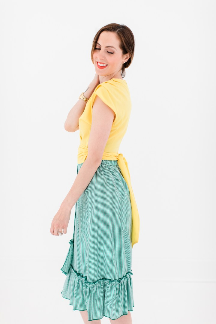Eva Amurri Martino wears a bright yellow wrap top and gingham ruffle skirt as part of a post about packing for a trip