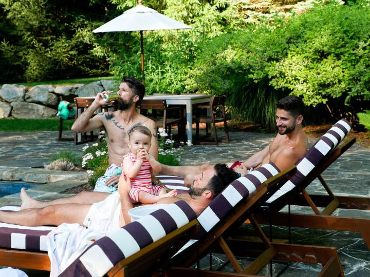Major Martino hangs out with a group of men, including father Kyle Martino beside the pool at their Connecticut home