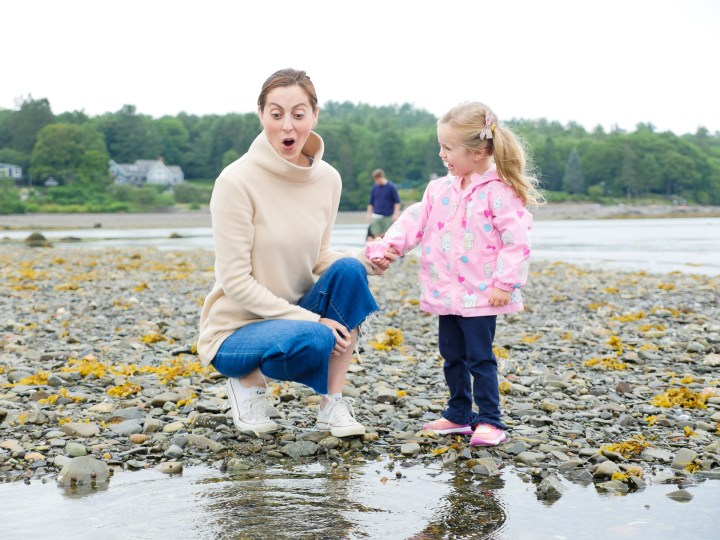 Eva Amurri Martino laughs and looks on as daughter Marlowe plays in the tidal pools on the beach in Maine