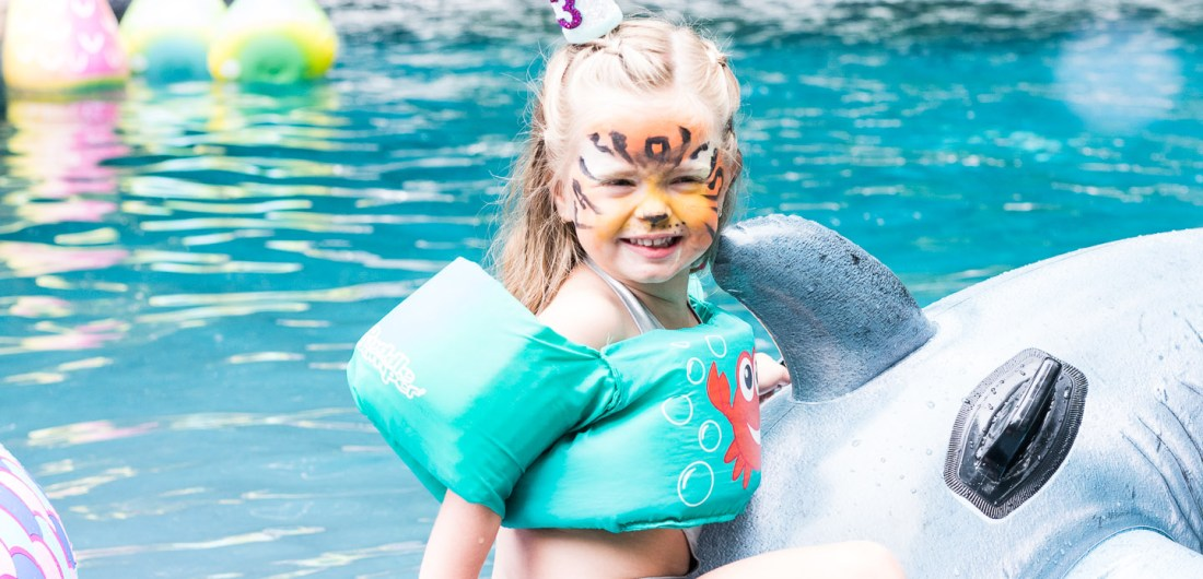 Marlowe Martino rides on a shark pool float in the pool of her Connecticut home at her third birthday party