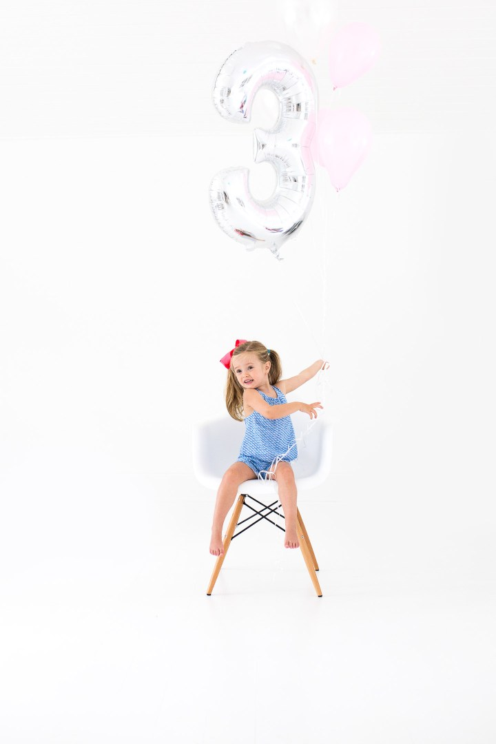 Marlowe Martino poses with a large balloon for her third birthday portraits