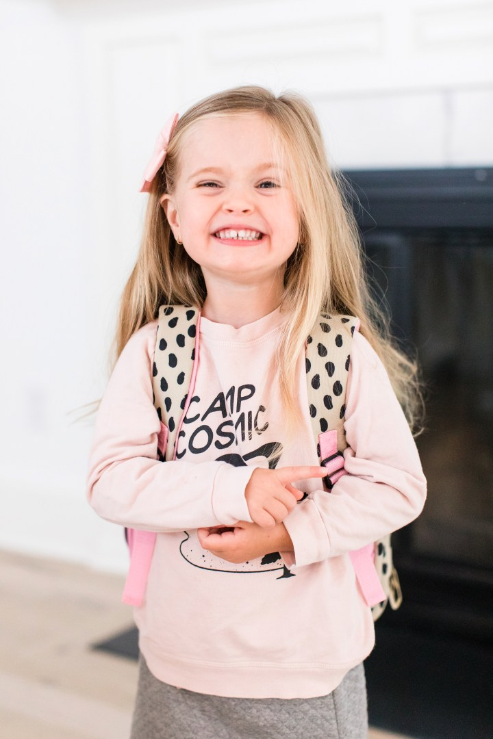 Marlowe Martino wears a pink sweatshirt and smiles as she gets ready for her first day of school