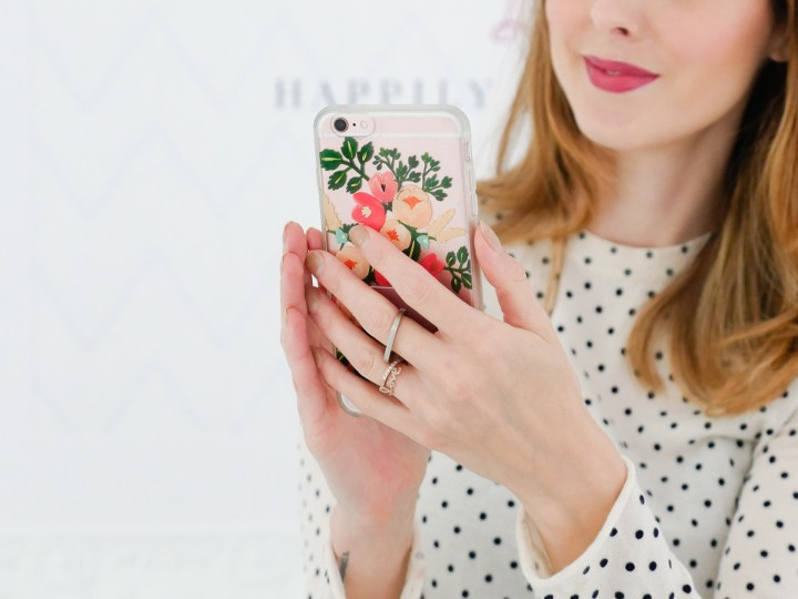 Eva Amurri Martino holds her phone with her finger slipped through the ring stand