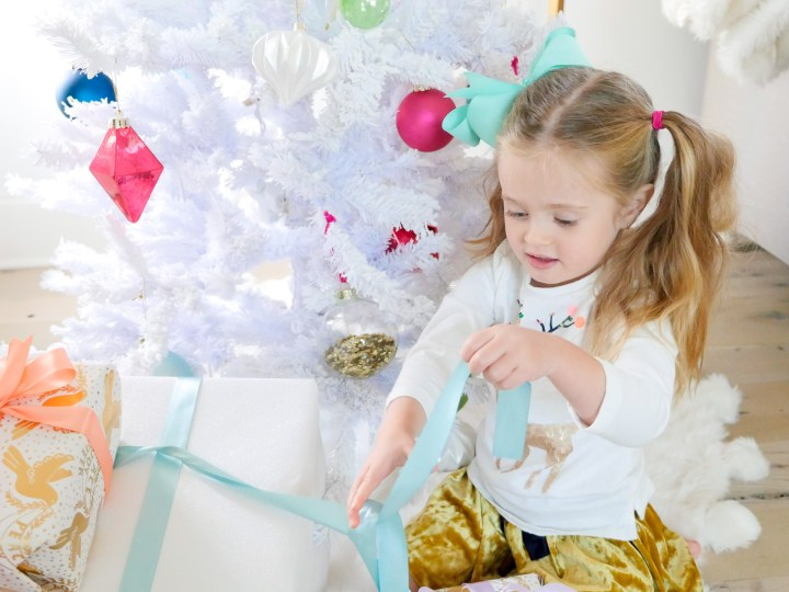 Marlowe Martino unwraps a colorful Christmas present in the family room of her Connecticut home
