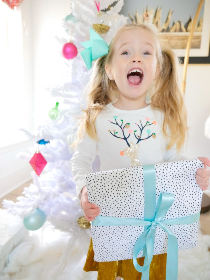 Marlowe Martino shrieks with joy as she holds a colorful christmas present in front of the white and pastel christmas tree in her Connecticut home