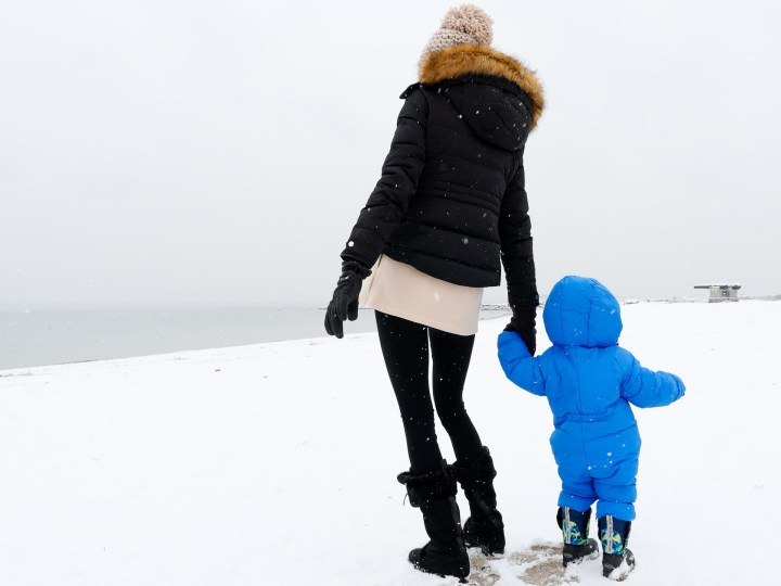Eva Martino holds son Major's hand as they walk through the snow on the beach in Westport CT