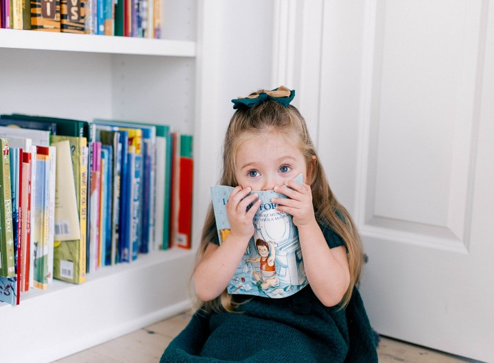 Marlowe Martino hides behind a book in the kitchen of her Connecticut home