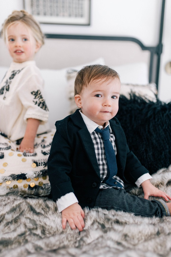 Major James Martino sits on his parents bed in a navy blue blazer and gingham shirt with his sister Marlow Mae Martino who is wearing an ivory smock dress at their house in Connecticut.