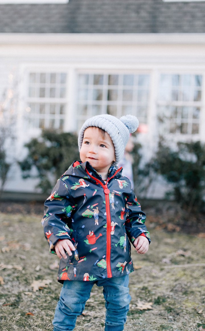 Major Martino wears a Peter Rabbit rain coat and a pom pom knit hat while he plays outside him home