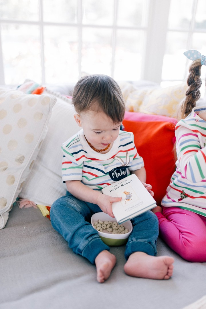 Major Martino wears a striped top and reads Peter Rabbit with a bowl of snacks