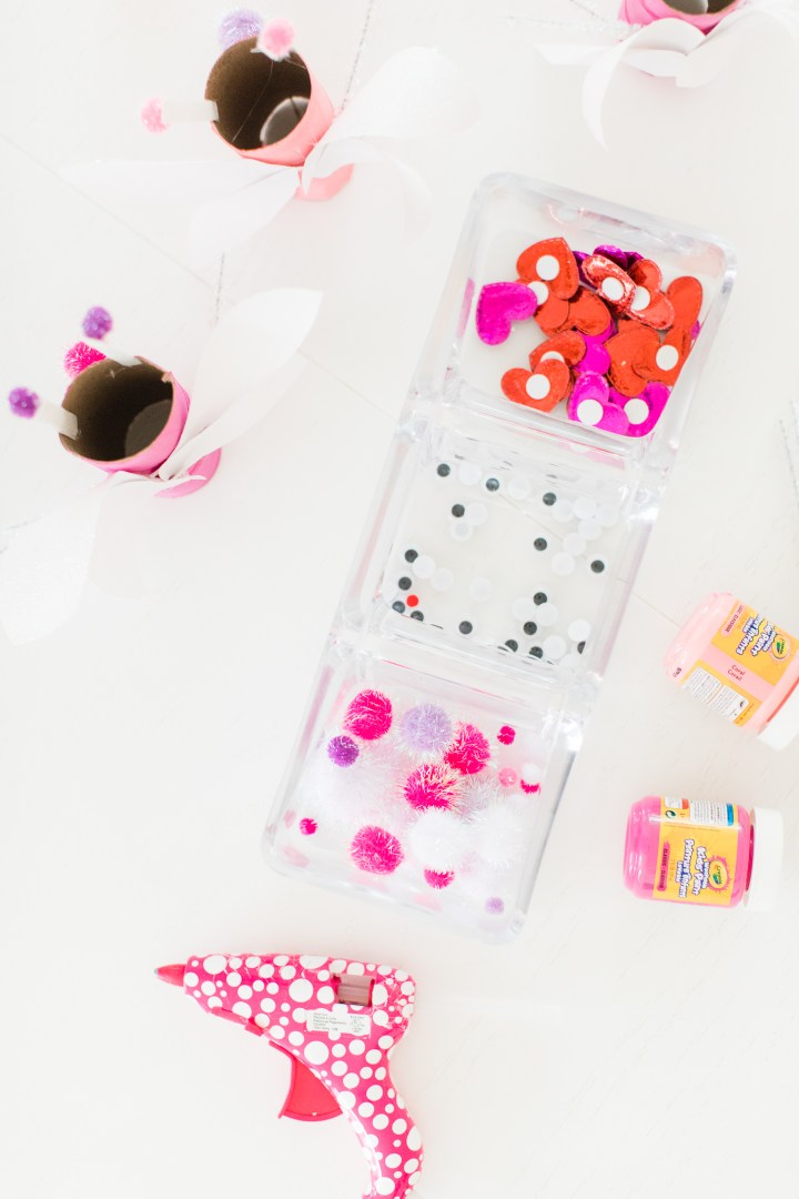 Pink, white, red, and sparkly materials to create DIY lovebugs