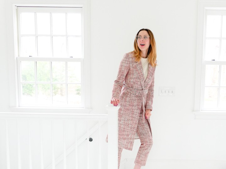 EVa Amurri Martino wears a red, white and black patterned coat and matching trousers, and walks up the stairs of her Connecticut home