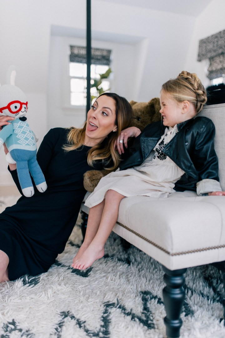 Eva Amurri Martino plays with a doll on the floor with her daughter Marlow Mae Martino who is wearing an ivory tunic dress, leather jacket, and halo braid.