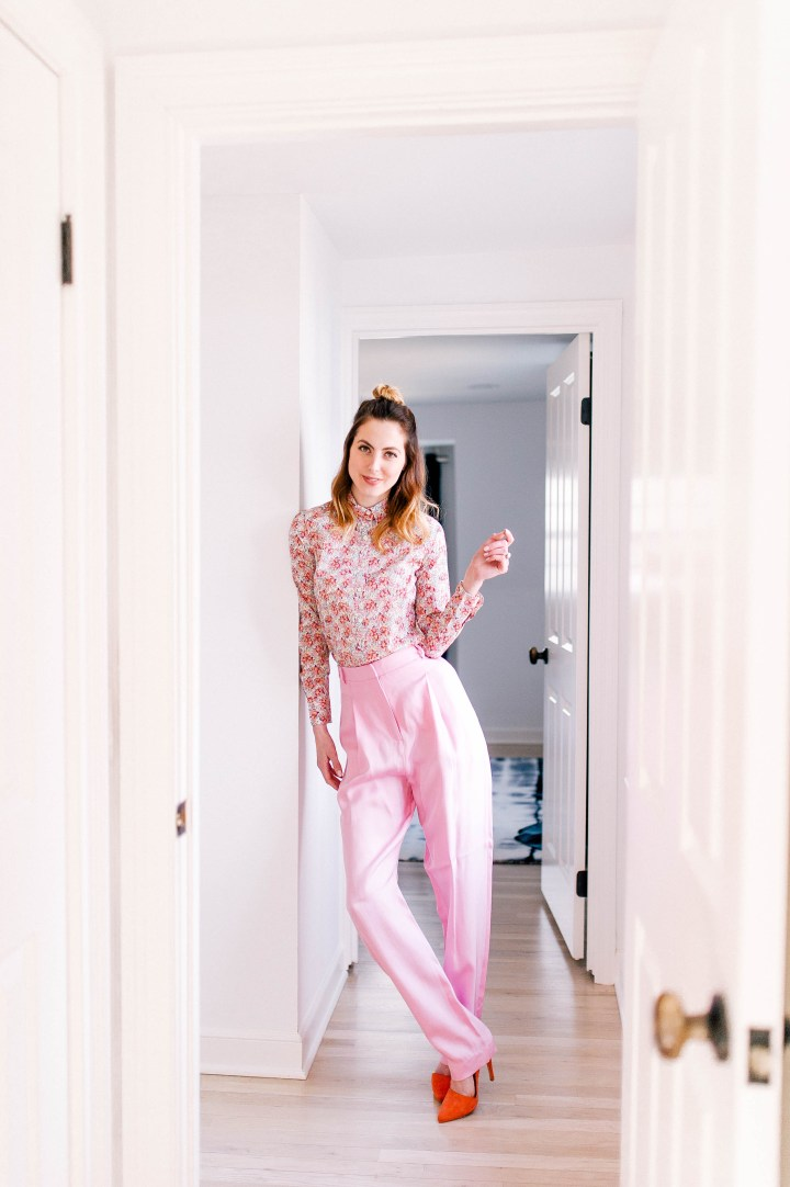 Eva Amurri Martino wears the hottest spring fashion trends: wide pink trousers, a pink floral button up shirt, and her hair in a half up half down topknot in her Connecticut home.
