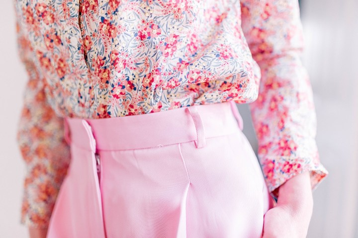A closeup of Eva Amurri Martino wears wide pink trousers, a pink floral button up shirt, and her hair in a half up half down topknot in her Connecticut home.