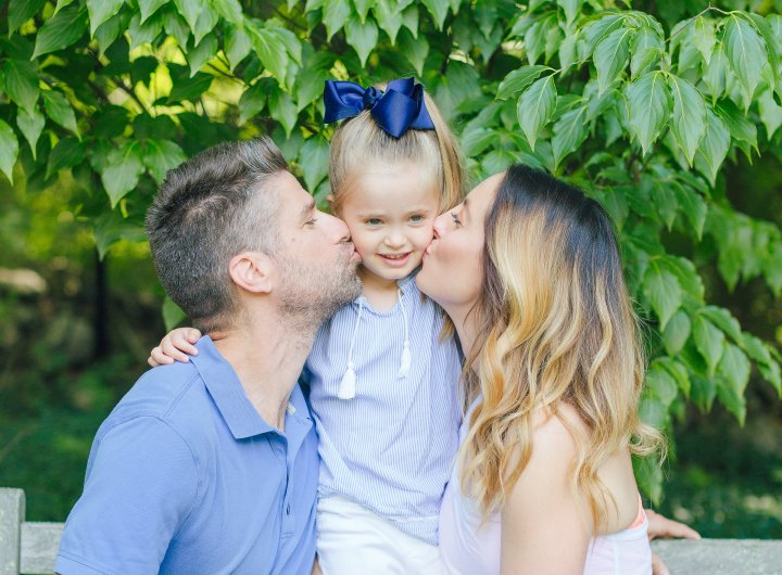 Eva Amurri Martino and Kyle Martino sit on either side of daughter Marlowe and kiss her on the cheeks