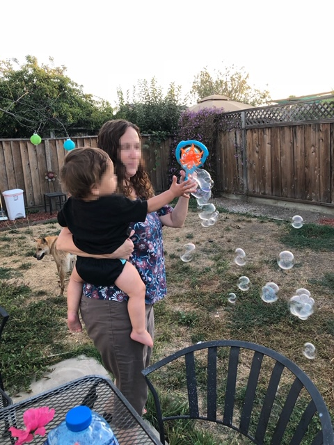 Activities for infants and toddlers blowing bubbles outdoors