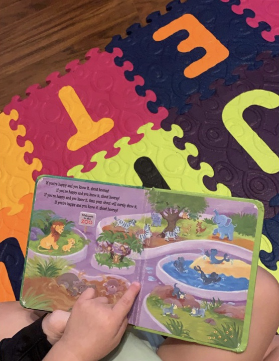 Activities for infants and toddlers reading a board book on colorful abc mat