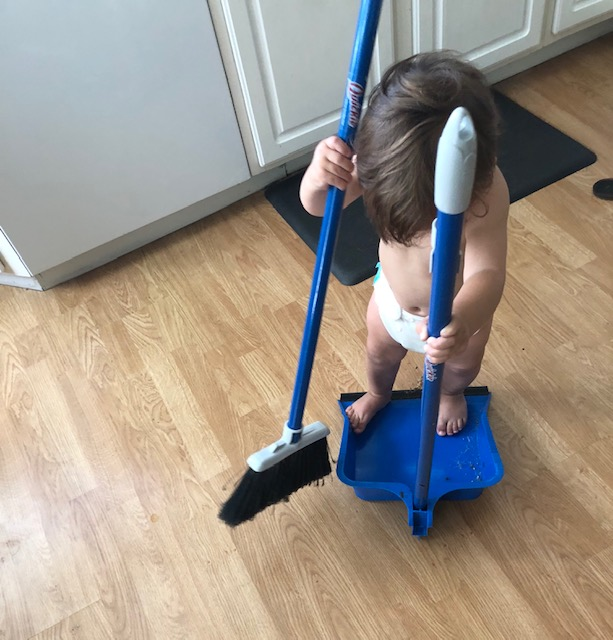 Activities for infants and toddlers helping sweep the kitchen