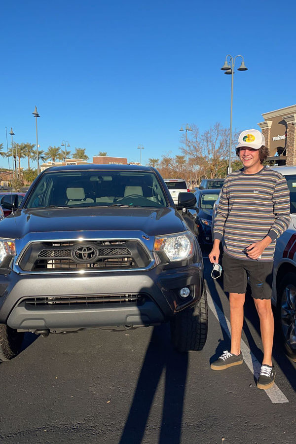 teen poses next to dream car