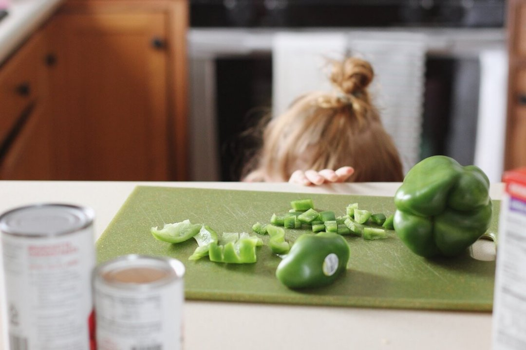 Blaire helping cook green peppers
