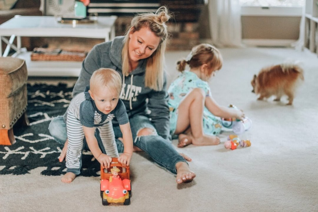 Mom playing with two kids in living room