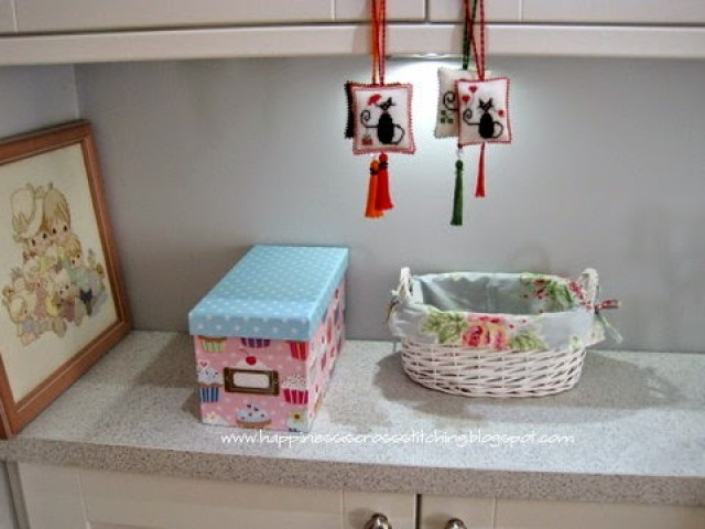 My craft room, pretty baskets and boxes adorn the top of the units. Hanging from the cabinet doors are pretty cross stitched scissor fobs that I hand made.