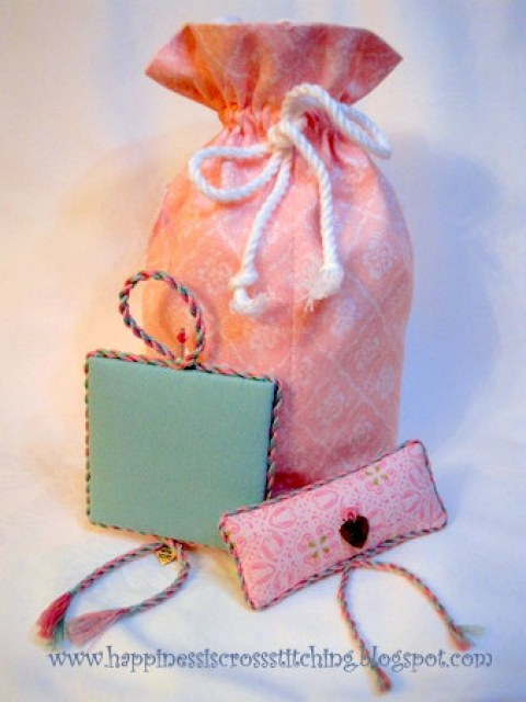 Pink cross stitched bag with matching pinkeep and pillow. The pinkeep has pale green fabric on the reverse  to compliment the letter S stitched in a soft green colour on the front.