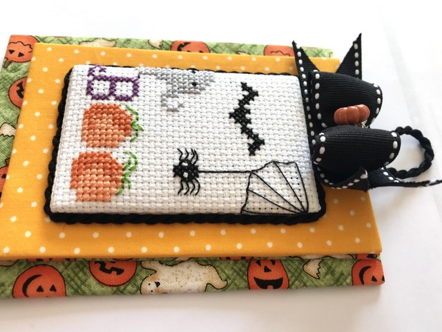 Boo Halloween Cross Stitch Pattern featuring two pumpkins with the letter B in front to spell Boo! A little ghost, a spider and two bats flying overhead.