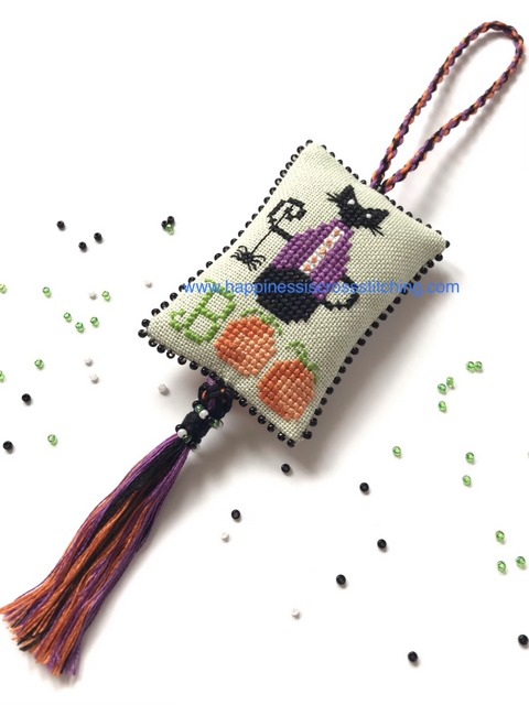Halloween stitching and thread holders. Mini black cat sat on two pumpkins, he is wearing a purple jacket and holding a spider. This is a cross stitched scissor fob with black beading around the edge.