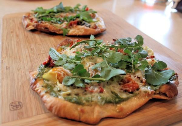 pita pizzas topped with arugula