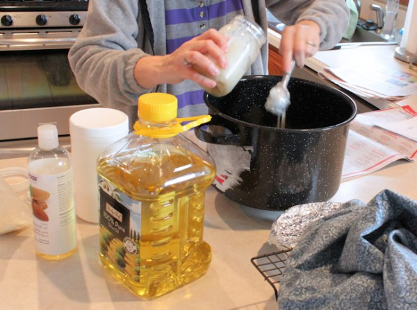 Lynda weighing the oils for soap