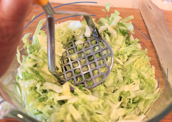 mashing cabbage to release the juice