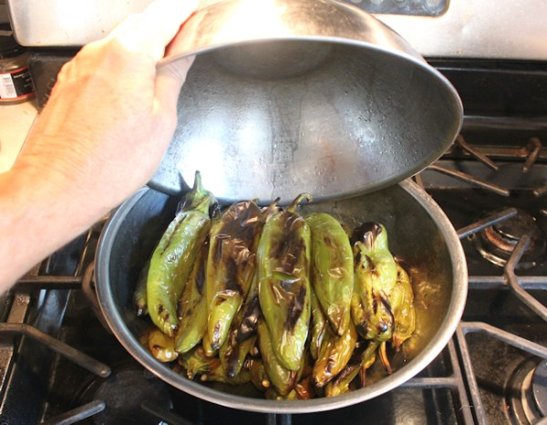 sweating the roasted chile peppers to loosen the skins