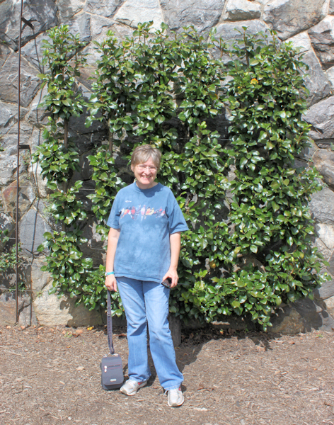 Lynda in front of espaliered fruit trees