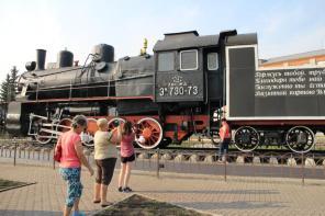 Russische Mitreisende fotografieren eine alte Lok am Bahnhof