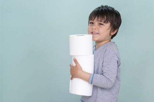 isolated-side-view-portrait-of-cute-kid-holding-toilet-roll-on-blue-background-child-boy-with-smiling-face-while-carrying-stack-of-toilet-paper-01-01
